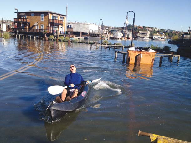 Jay McGill paddles his kayak down a flooded street near Waldo Point Harbor in Sausalito during a king tide in December 2012. Photo by Diana Vargas